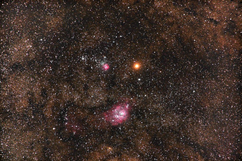 PENTAX-KPとTAMROM18-200mmズームレンズを使用して焦点距離300㎜(35mm換算)でISO12800/30秒を92枚加算平均コンポジットした2018年03月18日04時04分15秒から撮影したM8干潟星雲(下)とM20三裂星雲(上)の間を通過する火星の天体写真です。