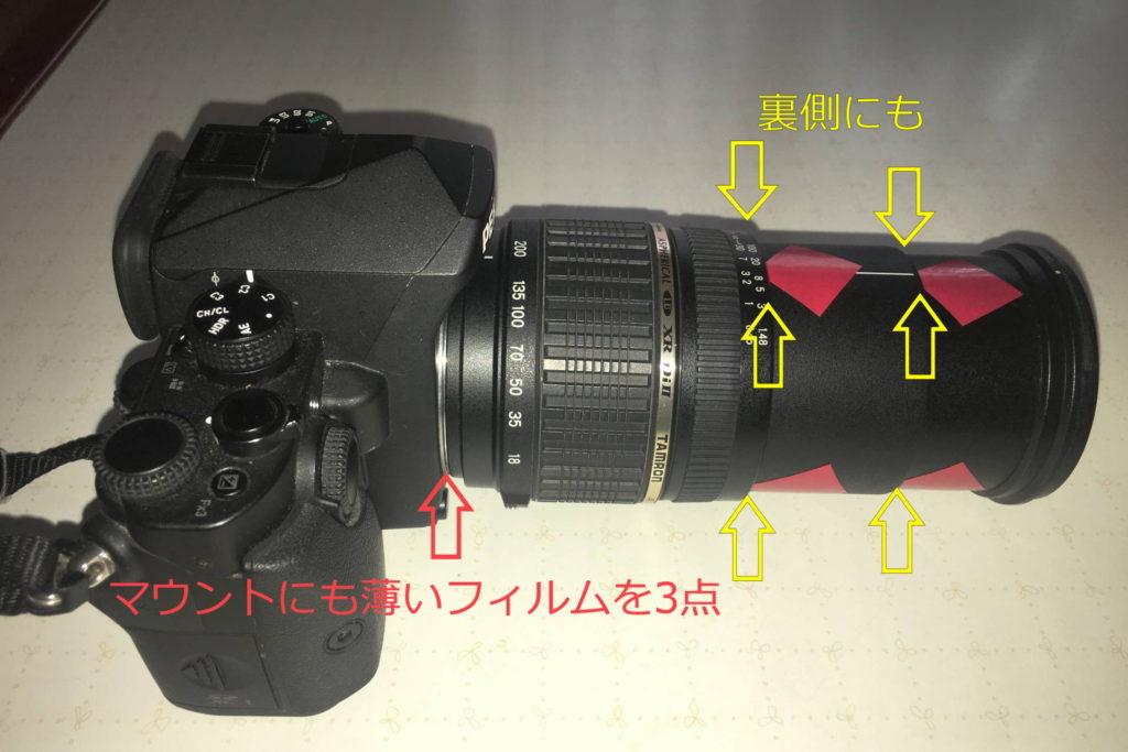 ズームの筒の部分にビニールテープを3点ずつ貼り、マウント部分にも薄いフィルムを3点挟んでカメラとレンズのガタを無くしています。